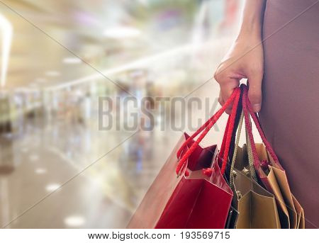 Woman holding shopping bags over shopping mall background with copy space.