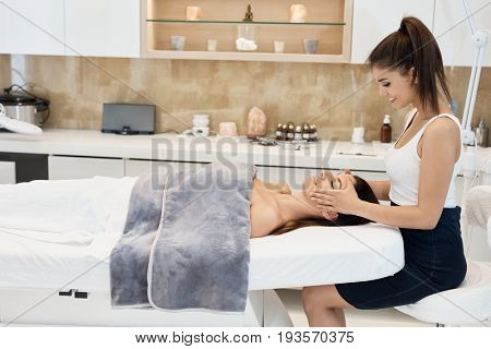 Young woman getting professional cosmetic treatment at beauty parlour.
