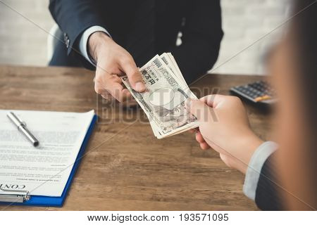 Businessman giving money Japanese yen banknotes to his partner while making contract - loan bribery and corruption concepts