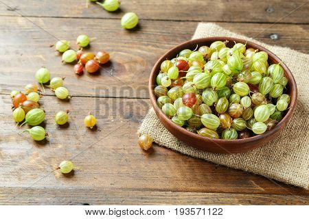 Ripe gooseberry in a brown clay plate and scattered next to a plate on a dark brown background space for text. Countryside picture of berry compote. Gooseberry multicolored