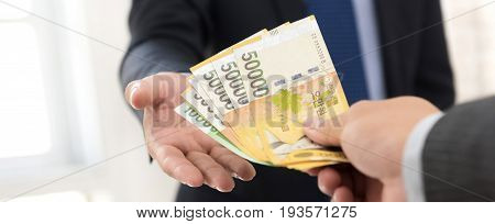 Businessman giving money South Korean won banknotes to his partner - panoramic banner