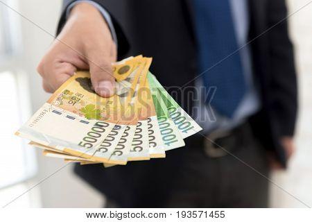 Businessman giving money South Korean won banknotes