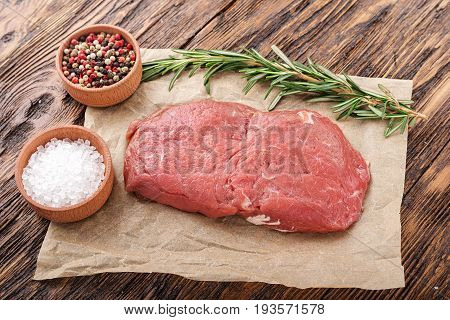 Steak with spices top view. Marble meat from veal there are pepper salt garlic and olive oil nearby