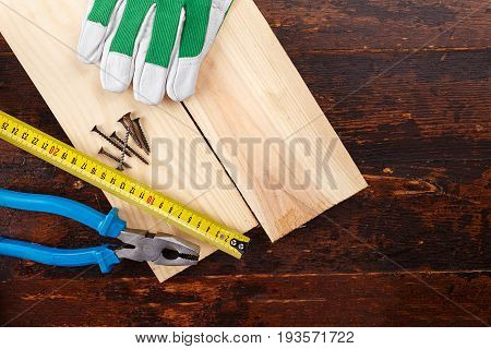 Working tools carpenter on a wooden background - ruler nails working gloves pliers. carpentry