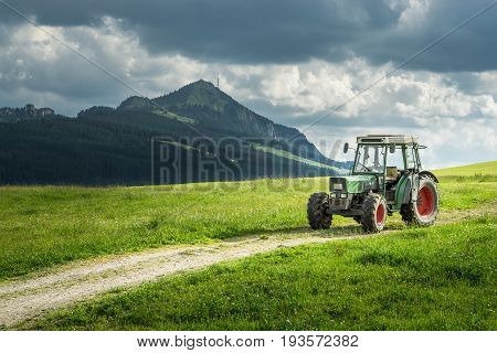 Old tractor on a meadow with fresh grass. Beautiful view to alpine mountains. Alps.
