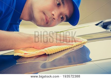 A man polishing car with microfiber cloth car detailing (or valeting) concept vintage tone image