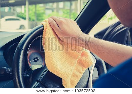 A man hand cleaning car steering wheel with microfiber cloth auto detailing (valeting) concept vintage tone image