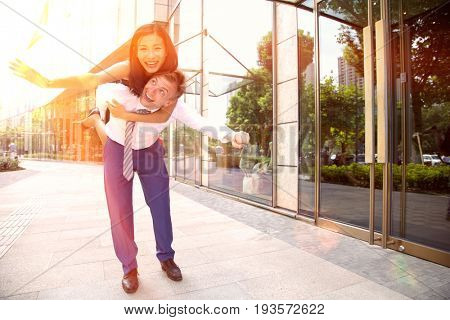 Business man giving chances woman a piggy back