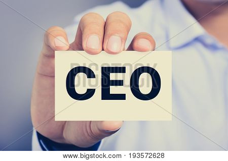 CEO letters (or Chief Executive Officer) on the card held by a man hand vintage tone