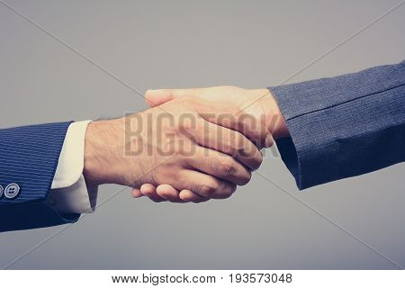 Handshake of businessman and businesswoman on light gray background vintage tone - greeting dealing merger and acquisition concepts