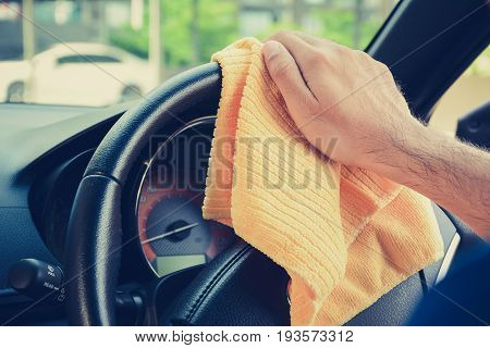 Hand cleaning car steering wheel with microfiber cloth auto detailing (valeting) concept