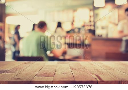 Wood table top on blur background of coffee shop interior with some people vintage tone - can be used for display or montage your products