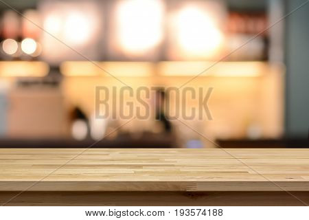 Wood table top on blur cafe ( coffee shop) interior background - can be used for display or montage your products