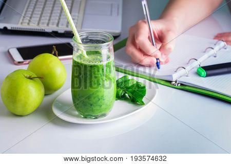 Woman right hand writing on notebook and laptop mobile smart phone nearby. Healthy Drink Smoothie from Green Spinach