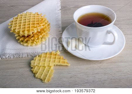 Breakfast with white cup of black tea with waffles stack on napkin and pieces of waffle on wooden surface.