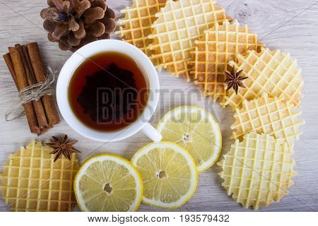 Cup of tea with Christmas decor, waffles and cinnamon, lemon, badian, pinecone