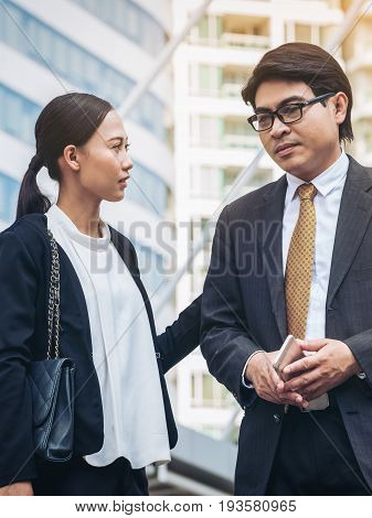Unhappy businessman and businesswoman speaking feeling nervous due to bad news and depression of businesses.