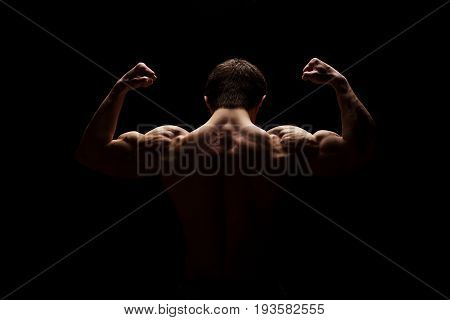 Strong muscular man showing his hands, shoulders, neck, bicep and back muscles. Fitness concept. Dramatic light.