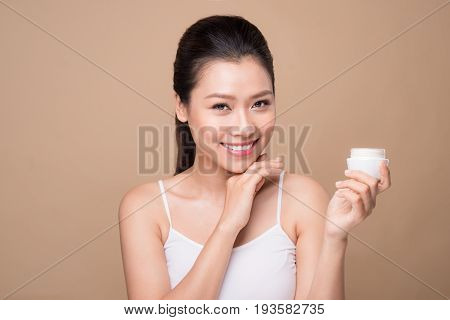 Skincare. Beautiful asian woman shows moisturizer or lotion product.