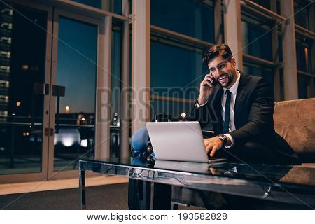 Smiling Businessman With Laptop Talking On Cellphone At The Airp