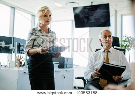 Senior businessman sitting in chair with female secretary standing by. Caucasian business colleagues in office looking away.