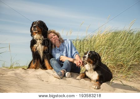 mature woman with her dogs on sand and grass sitting