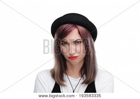 young offended girl in black hat looking at camera isolated on white