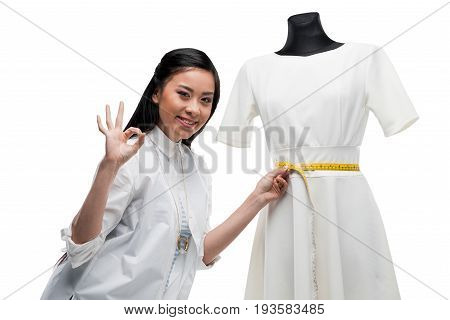 Happy Young Asian Dressmaker Measuring White Dress And Showing Ok Sign, Isolated On White