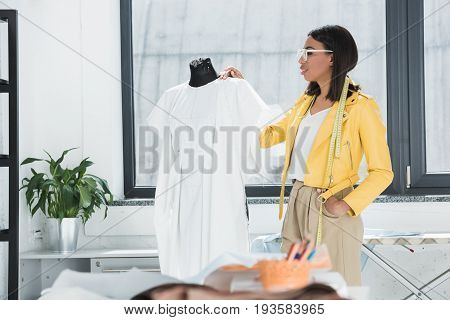 Young Woman In Spectacles And Measuring Tape On Neck Looking At Fashionable White Dress On Dummy