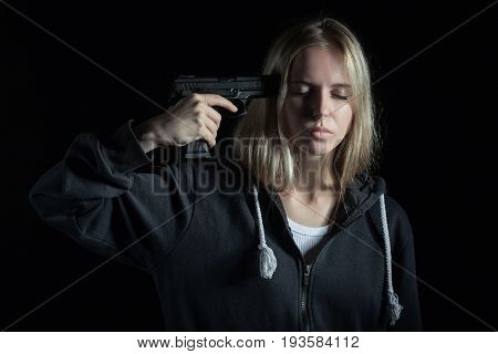 serious girl shooting herself on black background