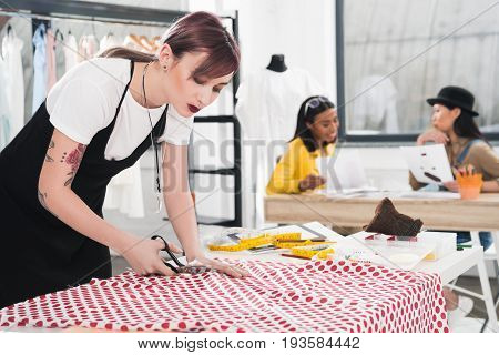 Young Caucasian Dressmaker Cutting Polka Dot Fabric While Her Colleagues Talking On Background