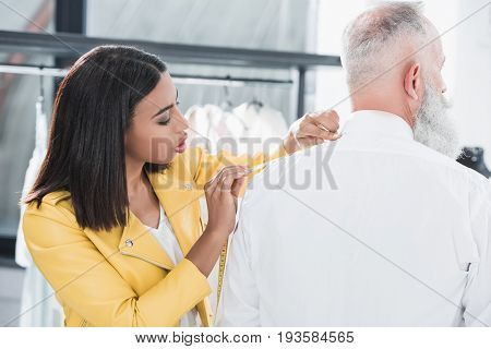 Young Tailor Measuring Senior Man With Tape Measure Indoors