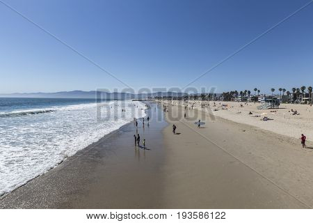 Los Angeles, California, USA - June 26, 2017:  Summertime view of people enjoying the sand and surf at Venice Beach, California.