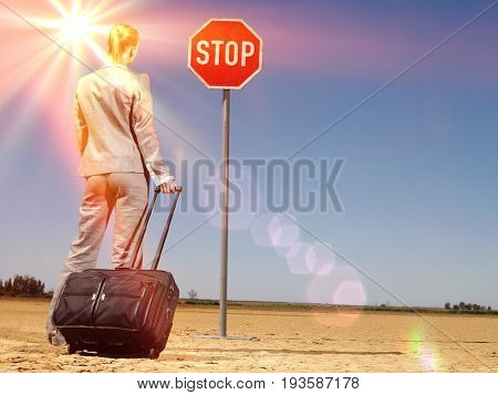 Rear view of young businesswoman with luggage looking at stop sign on desert