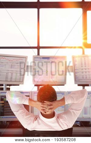 Rear view of stock trader with hands behind head watching multiple monitors