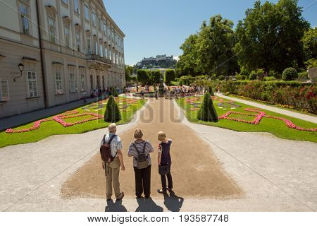 tourist standing infront of famous Mirabell Gardens with the old historic Fortress Hohensalzburg in the background in Salzburg Austria