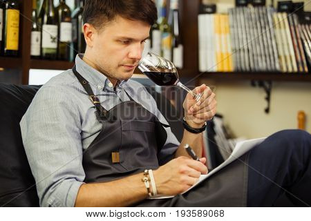 Male sommelier tasting red wine and making notes. Profession in winemaking. Man waiter with long-stemmed wineglass sitting in chair and drinking alcohol beverage