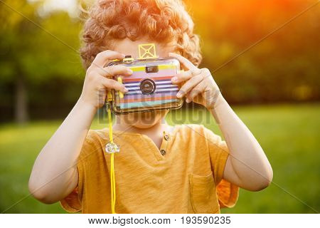 Little kid holding camera in hands standing in middle of meadow taking picture aiming at camera.