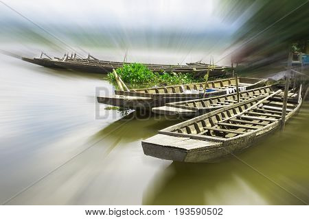 the wonderland of wooden boat float in reservoir with halo light for abstract background or mystery