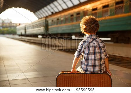 Young boy wearing check shirt sitting on brown suitcase at railroad station exposed to light.