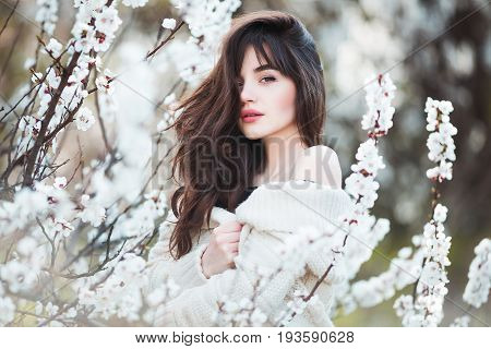 Happy beautiful young woman with long black healthy hair enjoy fresh flowers and sun light in blossom park