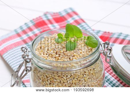 jar of pearl barley on checkered place mat - close up