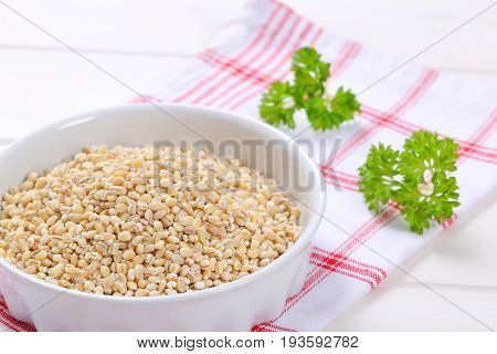 bowl of pearl barley on checkered dishtowel - close up