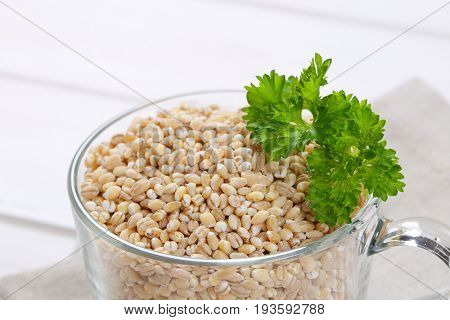 cup of pearl barley on on beige place mat - close up