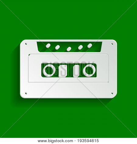 Cassette icon, audio tape sign. Vector. Paper whitish icon with soft shadow on green background.