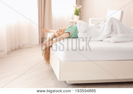 Morning of beautiful young woman lying on bed at home
