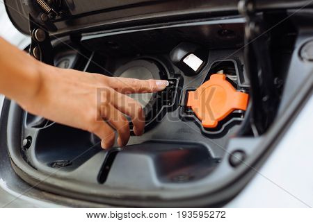 Car care. The close up of a dainty neat female hand pointing at the orange lid covering the charging unit with her index finger as if being ready to open it
