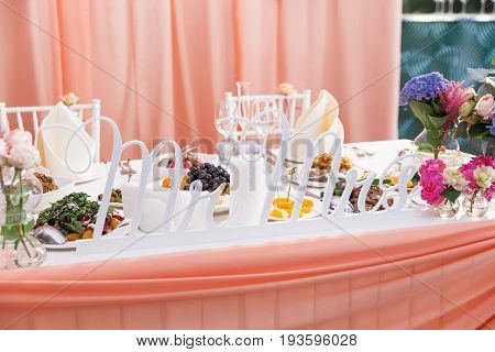 Table set for wedding banquet with floral composition of roses and hydrangea. Wooden carves letters Mr and Mrs symbol of marriage.