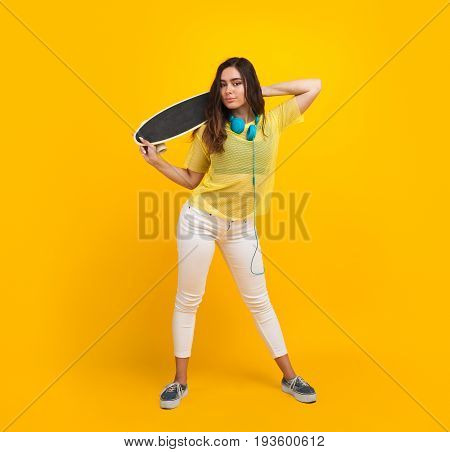 Brunette teenage girl in sheer shirt holding skateboard looking at camera.