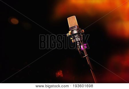 Microphone on orange background. Retro microphone. A microphone on stage. A pub. Bar. Restaurant. Classic. Evening. Night show. European restaurant. European bar. American restaurant. American bar.